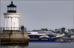 Spectators watch from Bug Light as The Cat leaves Portland Harbor on its first run of the season.