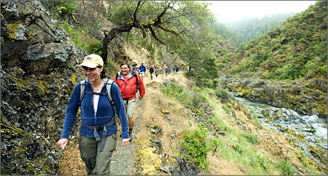 Leaving their worries  and tents  behind: Tami and Tom Vallee of Vallejo, Calif., walk along the river with other Rogue Wilderness Adventures hikers.