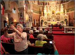 Jean Smith of Macedonia, Ohio snaps a photo of St. Casimir Catholic Church during a tour in Cleveland. Since plans to close the old Polish church were announced, tourists have arrived to see an architectural masterpiece that includes what some call the most beautiful altar in northeast Ohio.