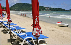 Visitors stroll along a nearly empty beach in Phuket, Thailand last month; travel businesses are rolling out deals hoping to combat a tourism decline fueled by the global recession and swine flu fears.