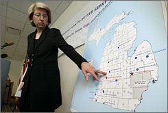 Michigan Secretary of State Terri Lynn Land gestures to a map of Michigan.  Rep. Michael Lahti wants to make sure both peninsulas are shown in all of state government's official publications.