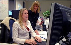 Kathy Hall-Zientek, manager of the in-house travel agency at Moog, Inc., watches as Krista Tortorice books a reservation.