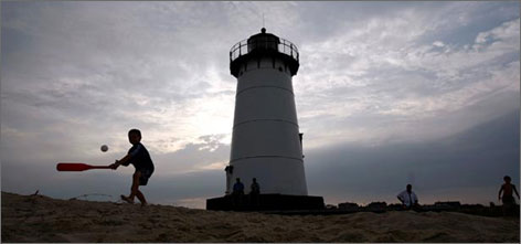 Simple pleasures: A boy joins his brothers in a game of Wiffle ball in front of the Edgartown Lighthouse as the sun sets.