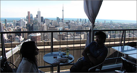 Living the high life: Sister and brother Prasidha and Pradyut Pratap drink in the views of downtown from the Panorama lounge on the 51st floor of the Manulife Centre.