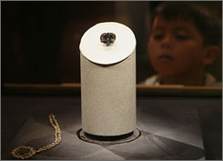 A young visitor cranes to get a glimpse of the 45.52-carat Hope Diamond, displayed for the first time ever with no setting to mark the 50th anniversary of its acquisition by the Smithsonian's National Museum of Natural History in Washington. 