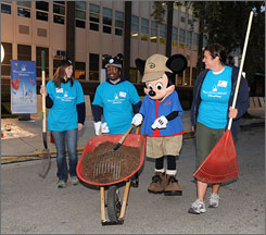 "With a little help from Mickey Mouse, Danielle Rub, Dwayne Gibson and Marissa Sproul volunteer at the Bethune School of Excellence in Chicago to help kick off the ""Give a Day, Get a Disney Day"" program."
