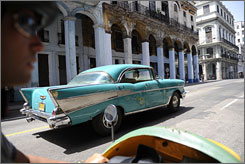 Quintessential Cuba: Vintage American cars predating the U.S. trade embargo roll past colonial architecture that has made Old Havana a UNESCO World Heritage site.
