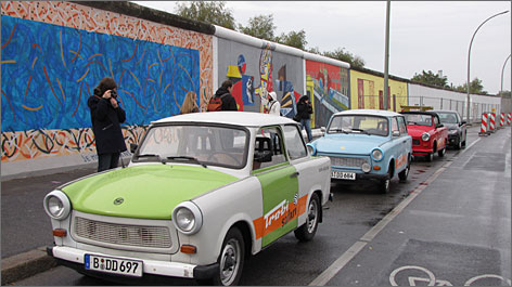Mini-mobiles: Trabis line up along East Side Gallery. Trabi-Safari tour company leads sightseeing trips in tiny Trabants, which became synonymous with socialist ineptitude.