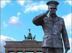 Salute to history: A living statue greets visitors at the Brandenburg Gate, the symbol of Berlin.
