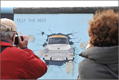 Visitors snap a photograph of a painting on a segment of the reopened East Side Gallery in Berlin. Over the past year, nearly 90 artists from around the world gathered again to repaint their original Berlin Wall creations.