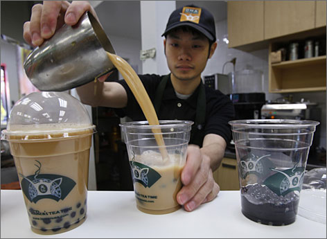 An employee at Ten Ren Tea in Flushing, N.Y., pours servings of bubble tea. Ten Ren sells many other types of tea, including an  oolong that costs $110 for an 11-ounce  bag.