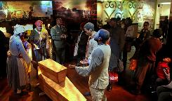 A scene depicting an African burial ceremony attracts a crowd during the grand opening of the African Burial Ground National Monument's new visitor center in New York.