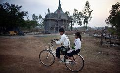 Students make their way past the tomb of former Khmer Rouge leader Ta Mok in Anlong Veng, Cambodia.