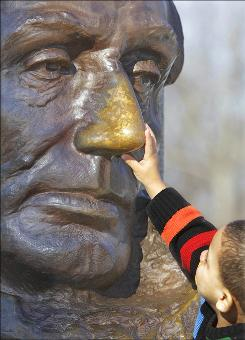 Springfield, Ill.: Jordan Seoniers of Houston goes straight for the good-luck charm of the statue at Abraham Lincoln's tomb.