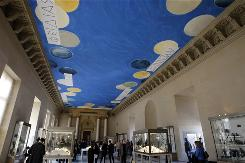 The Cy Twombly-designed gallery ceiling  at The Louvre features a deep blue background punctuated with floating disks and emblazoned with the names of sculptors from ancient Greece.