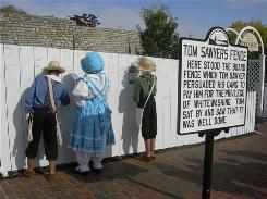 Children dressed as Tom Sawyer and Becky Thatcher sign the famous white picket fence in Hannibal, Mo.