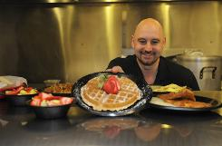 Owner George Gallis shows off some of the dishes that helped Nishie G's Cafe land a spot on Southern Living's list of best breakfasts in South Carolina.