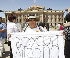 Josephine Nevarez, of Phoenix, holds a sign in protest as she attends a news conference where it was announced that The National Coalition of Latino Clergy and Christian Leaders, with the support of several other activist groups, had filed a lawsuit seeking an injunction preventing authorities from enforcing the new Arizona immigration law at the Arizona Capitol in Phoenix.