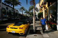 Signs of affluence: A Ferrari parked along Rodeo Drive is one, as is the high-priced, exclusive real estate.