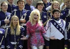 Full circle: Entertainer Dolly Parton poses with the Sevier County High School marching band. Parton was in the band when she was in high school.
