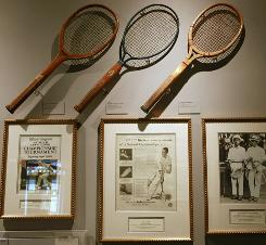 Tennis rackets from the 1920s are displayed above historic photos.