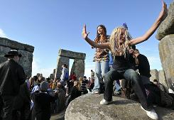 A crowd celebrates at Stonehenge as the sun rises on the summer solstice.