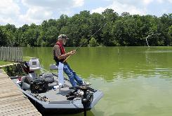 Billy Hinton of Birmingham, Ala., fishes near the dock at Ray Scott's Trophy Bass Retreat in Montgomery.