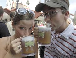 Park guests Jillian Woodworth and Steven Hopke try butterbeer at the Wizarding World of Harry Potter at Universal Orlando.