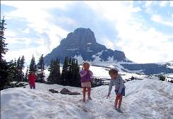 Along Going-to-the-Sun Road: Youngsters frolic in midsummer snowdrifts near 6,646-foot-high Logan Pass.
