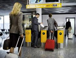 Travelers scan their tickets at an automatic boarding gate in Frankfurt; while common in Europe, Continental is the first U.S. airline to try a similar procedure with a single self-boarding gate in Houston.