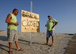 Dennis Hoyer, left, and Andy Porter chat near a sign announcing a beach closure in Grand Isle, La., Monday, May 24, 2010. Local authorities closed the beaches on the island after oil from the blown-out BP well began to wash ashore.