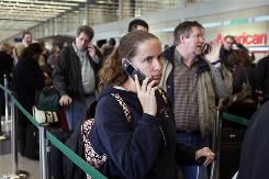 Passengers talk on their cellphones while waiting to rebook canceled flights at Chicago O'Hare Airport. Surveys have found most airline passengers do not want to sit in close proximity to fellow travelers chatting it up on cellphones.