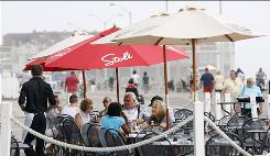 People lunch along the boardwalk in Asbury Park, N.J. New bars and cafes, a pinball museum and a water park for kids are hallmarks of the city's resurrection.