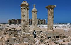 With a five-star hotel in the background, a man walks by restored Roman pillar tombs in the ancient city of Leukaspis in Marina, Egypt.