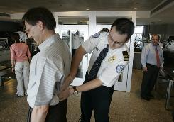 Matt Bulgur, a supervisor for theTSA at Dulles Airport, pats down a passenger after the X-ray machine turned up something questionable.