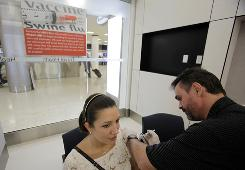Nurse Marcel Giguere gives a flu shot to Sandra Ghisays at the Airport MD clinic at Miami International Airport.