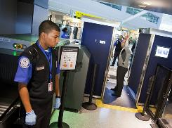 TSA officers demonstrate the full-body scanner at John F. Kennedy International Airport.