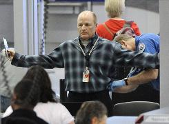 A traveler is patted down by a TSA agent at Chicago O'Hare. Most fliers in a new poll say they are either bothered or angered by the new airport security procedures.