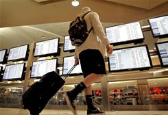 A traveler checks the arrivals and departures screens at Phoenix Sky Harbor International Airport. With signs of improvement in the economy, travel demand is on the rise.