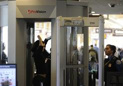 A passenger goes through a body scanner at a security checkpoint at Ronald Reagan Washington National Airport; a USA TODAY survey of frequent travelers shows strong objections to TSA's new screening methods.