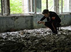 A tourist from Sweden takes picture of gas masks on a school floor in Pripyat on Sept. 16.