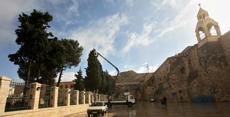 Workers of Bethlehem municipality begin decorating Manger Square, outside the Church of the Nativity, right, ahead of the town's planned Christmas celebrations. The numbers of visitors to the town have been rising steadily in recent years.