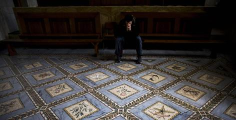 A Christian pilgrim pauses inside the Church of the Visitation, where a pregnant Mary is said to have visited her cousin Elizabeth, in the Jerusalem neighborhood of Ein Kerem.