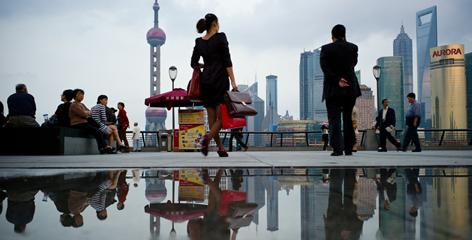 Pedestrians walk past the skyline of Shanghai's financial district in Oct. 2010.