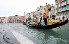 "A gondola passes near Rialto Bridge in Venice, Italy, in 2008. Avoid having to pay for an ""optional"" service by reaching out to employees in the customer-service center if there is a question about country-specific requirements."