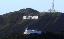 The famed Hollywood sign sits nestled in the hills surrounding it and the Griffith Park Observatory in Los Angeles.