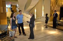 Hotel host Kristen Gleeson, center, checks in Peter O'Gorman, second left, and his sister Victoria O'Gorman, both of Dublin, at Hyatt's Andaz hotel in New York, July 2010.