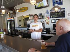 Daniel Estaffa serves a customer at his Hook'd Pier Bar &amp; Grill on the Panama City Beach Pier in Panama City Beach, Fla. 