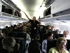 Flight attendants in the aisles during taxi are performing FAA-mandated demonstrations and seat belt checks. As soon as they are complete, the flight attendants are required to be seated.