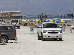 Vehicles drive along the beach in Daytona Beach, Fla., on Aug. 19, 2010.